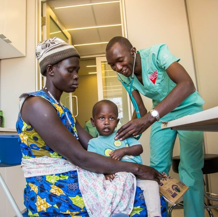 A Medical Teams staff member tends to a mother and her child inside the container clinic in Adjumani, Uganda.