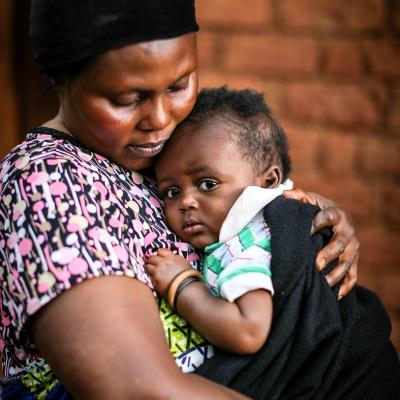 Suzanne holds her baby, Rwamba, in Tanzania.