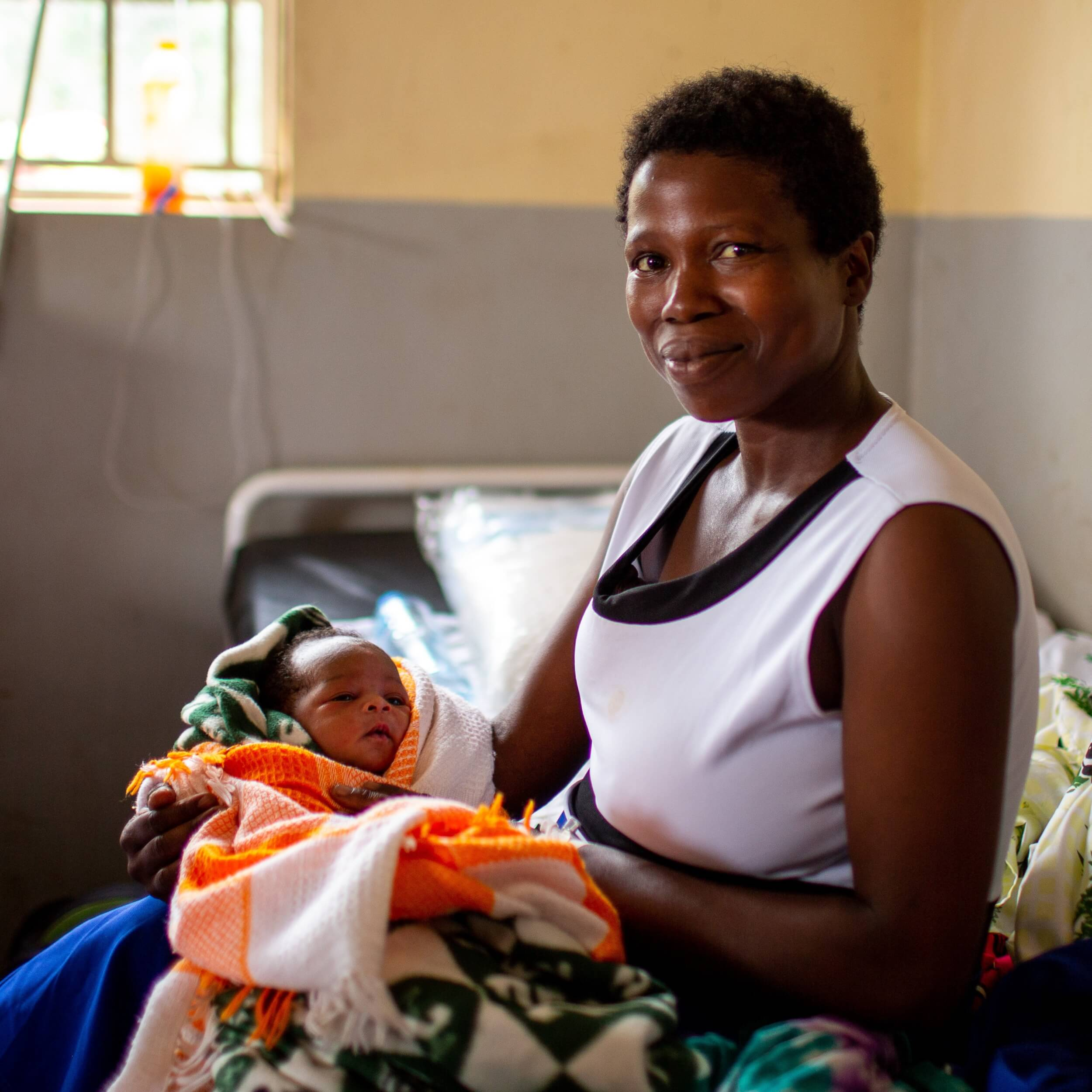 Florence holds her newborn in a medical clinic in Uganda.